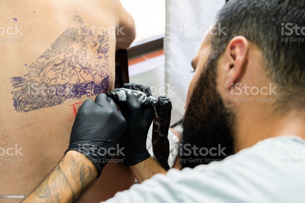 Professional Master Tattoo Artist Drawing Tattoos Picture On Mans