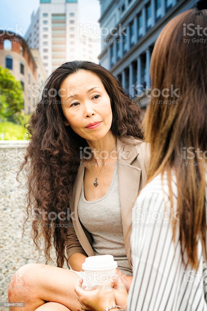 Professional mature Japanese woman listening to younger colleague stock photo