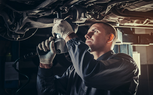Professional mechanic repairing a car in auto repair shop