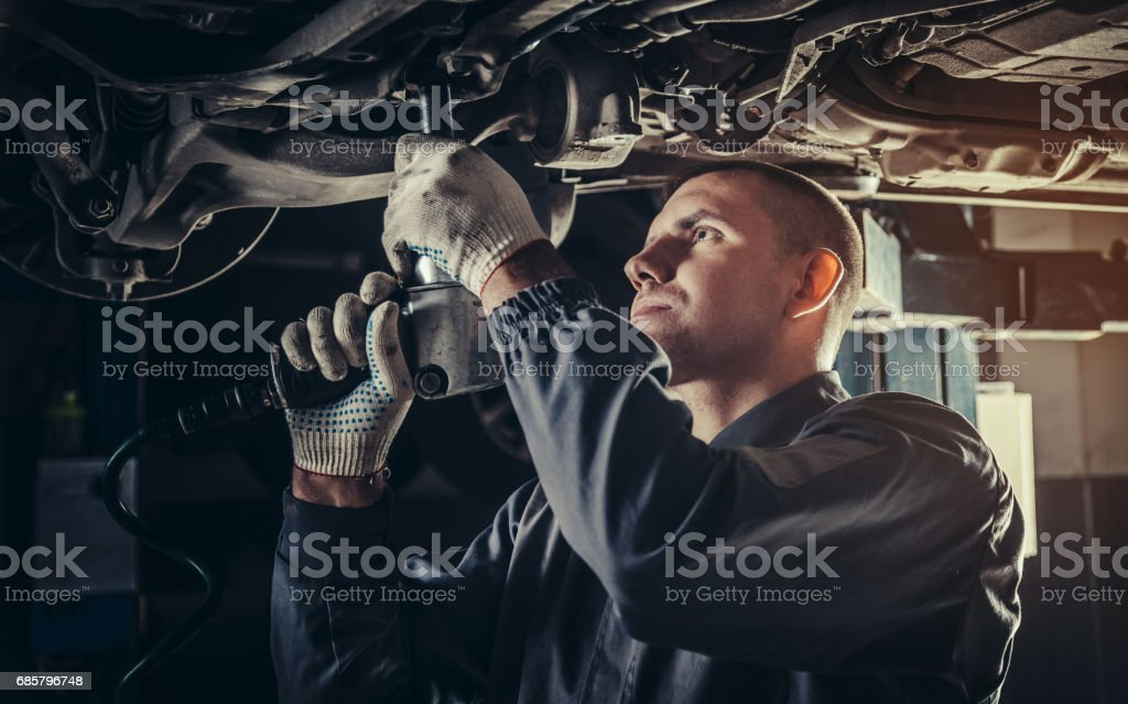 Professional mechanic repairing a car in auto repair shop stock photo