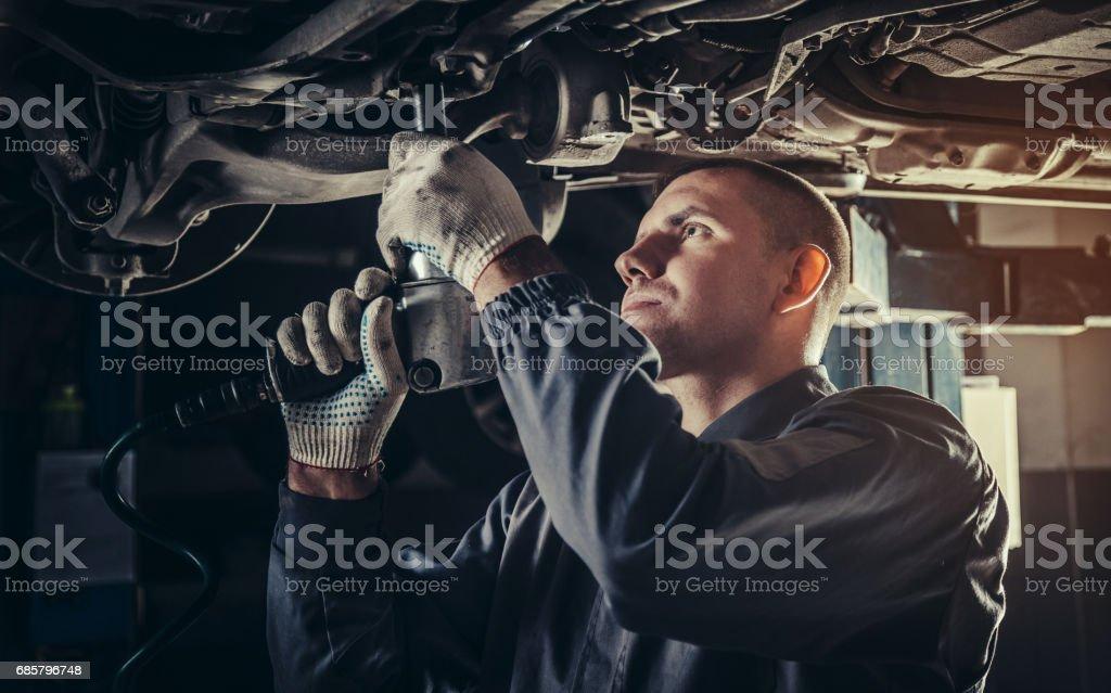 Mecánico profesional reparación de un coche en el taller de reparación de automóviles - foto de stock