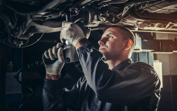 Professional mechanic repairing a car in auto repair shop Professional mechanic repairing a car in auto repair shop repairman stock pictures, royalty-free photos & images