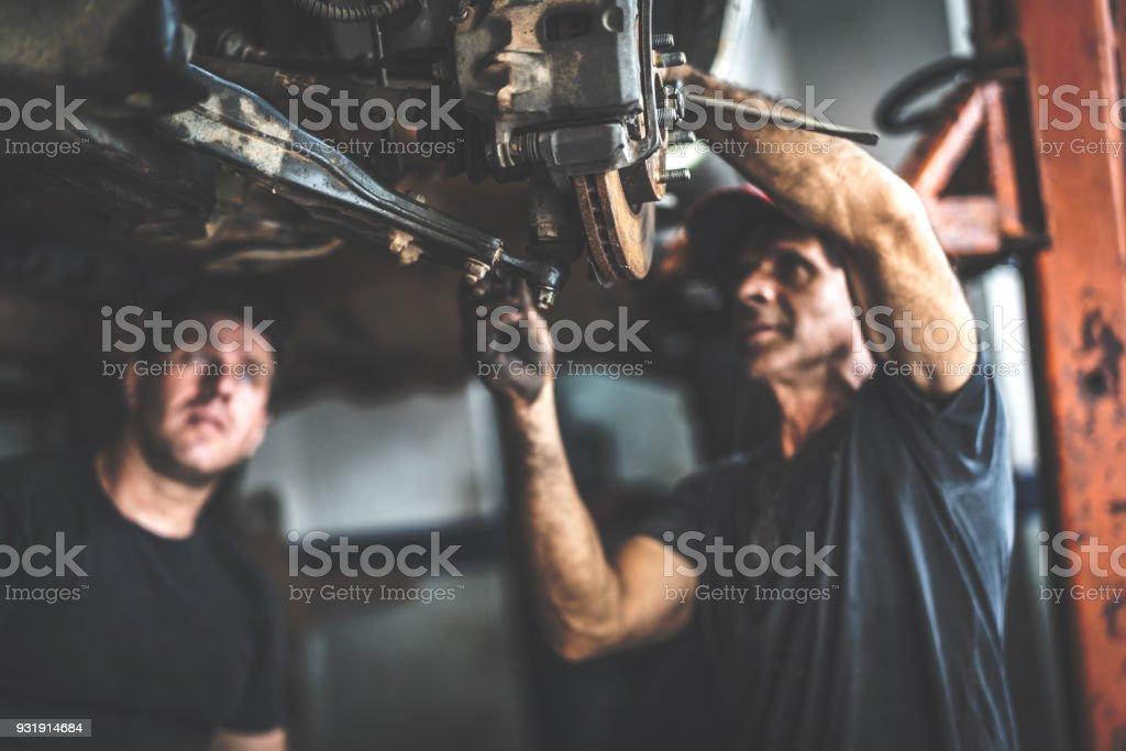 Professional mechanic repairing a car in auto repair shop stock photo