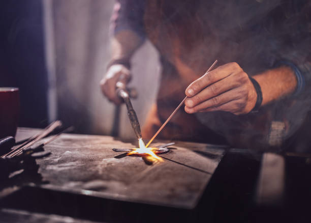 Professional mechanic soldering metal in workshop garage Close-up of blacksmith shop worker's hands melting and soldering metal for repair work in workshop soldering iron stock pictures, royalty-free photos & images