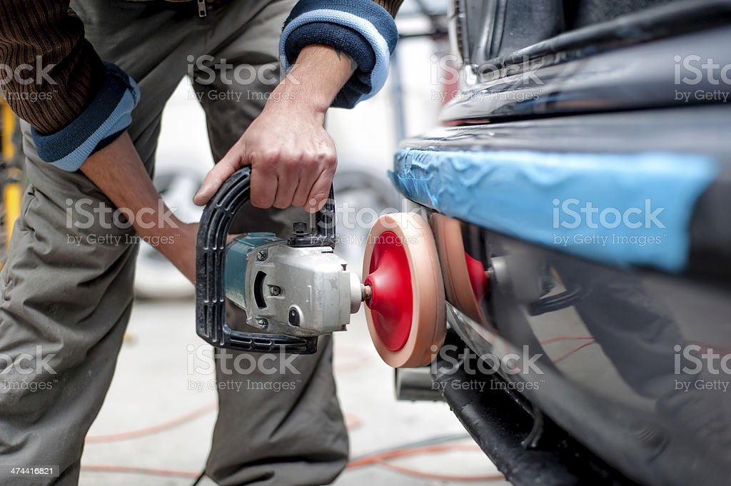 professional mechanic using a power buffer machine for cleaning stock photo