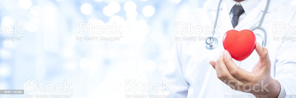 Professional medical doctor holding a red heart ball on blur office in the hospital and bokeh background. Concept of health care. stock photo
