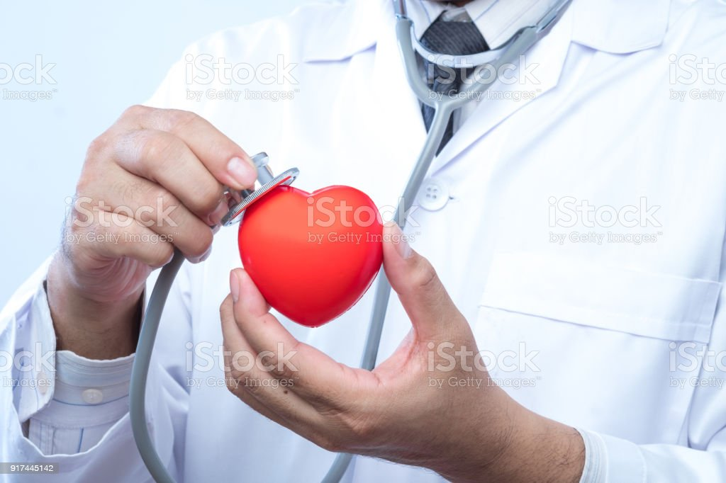 Professional medical doctor holding a stethoscope check up on a red heart ball. Concept of health care. stock photo