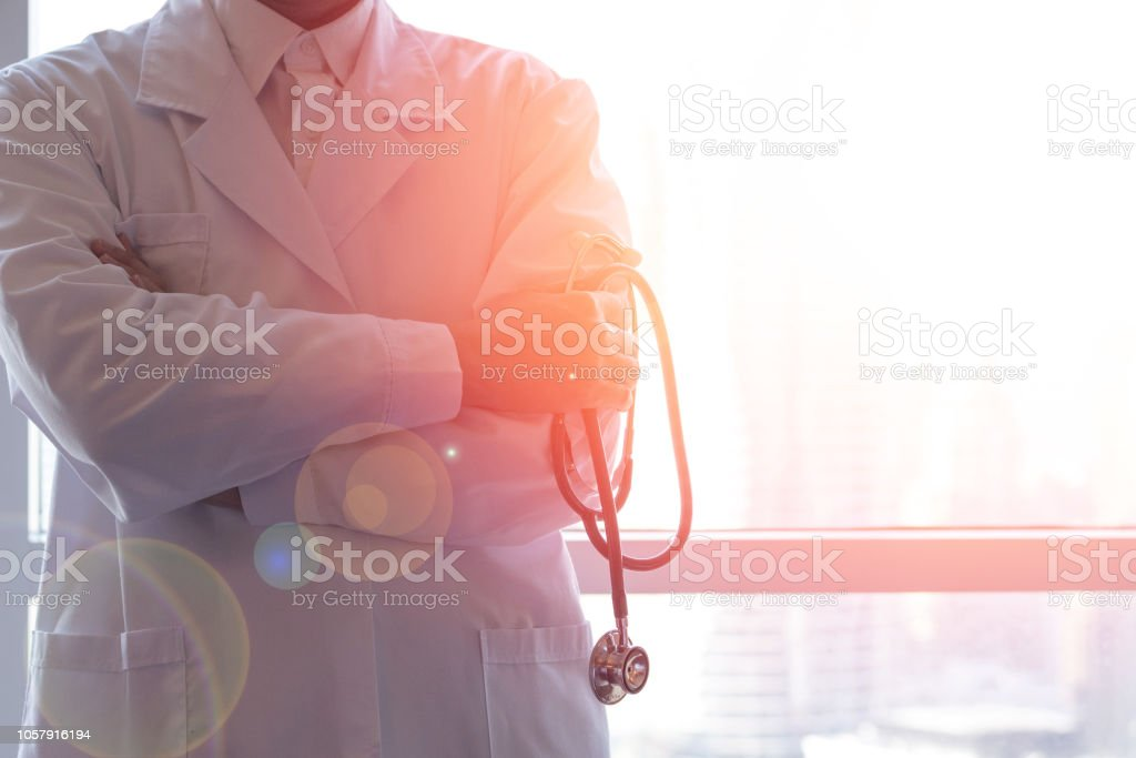 Professional medical physician doctor in white uniform gown coat hand holding stethoscope in clinic hospital.Medical/ healthcare/ technology concept stock photo