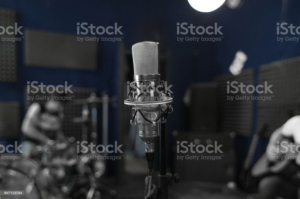 Professional Microphone on Stand with Blurred Recording Studio and Musicians as Background stock photo