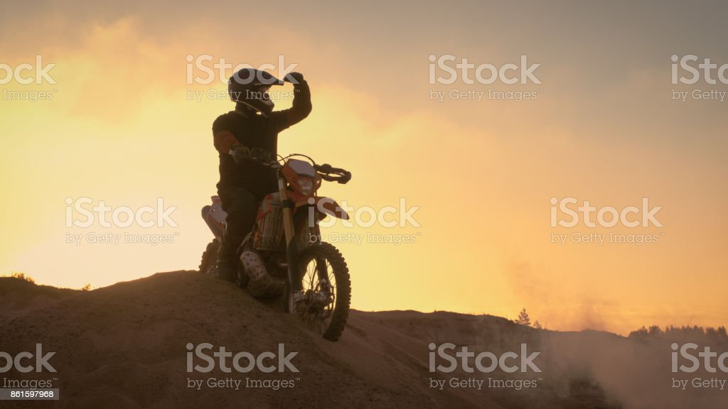 Professional Motocross Biker Spectacularly Stands on the Off-Road Dune on his Enduro Motorcycle. Looks Afar on the Whole Track. stock photo