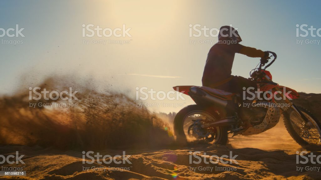 Professional Motocross FMX Motorcycle Rider Drives in Circles on the Off-Road Deserted Quarry. stock photo