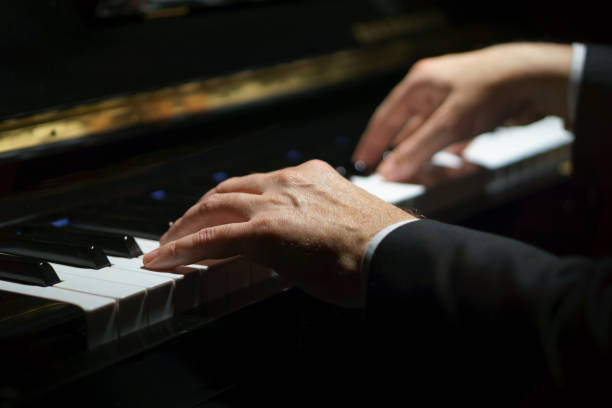 Professional musician pianist hands on piano keys of a classic piano in the dark. Professional musician pianist hands on piano keys of a classic piano in the dark. pianist stock pictures, royalty-free photos & images
