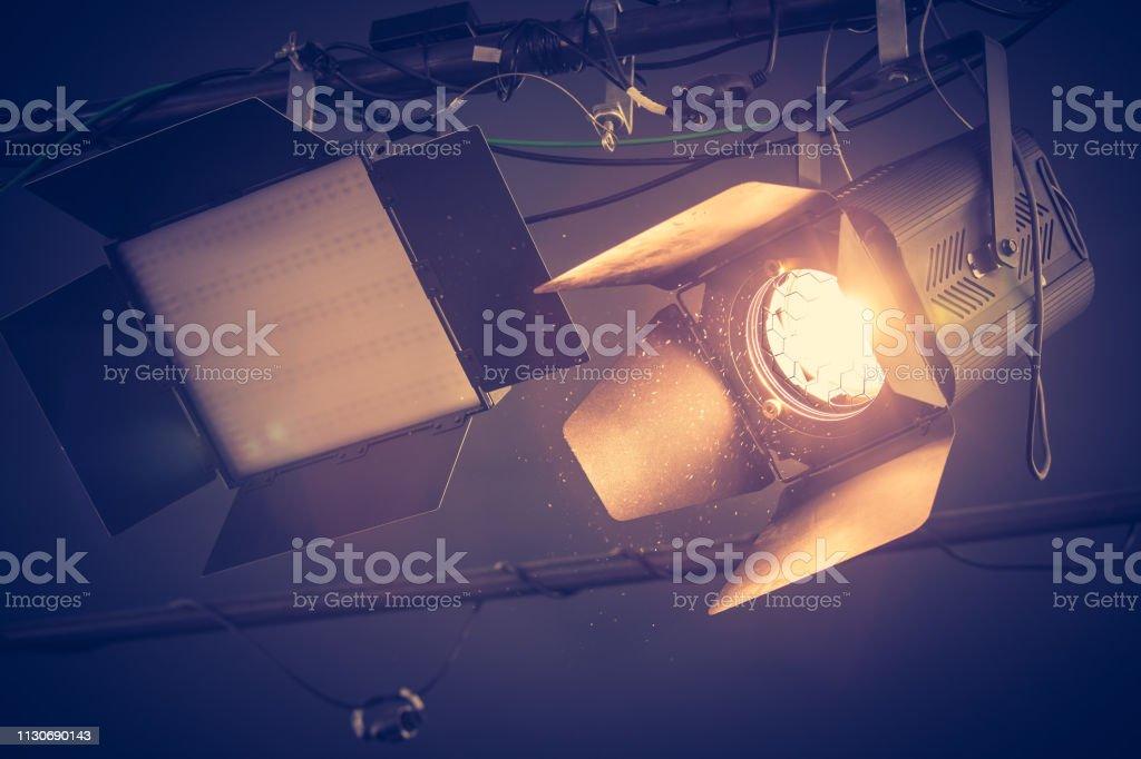 Professional orange studio spotlight hanging on the ceiling.