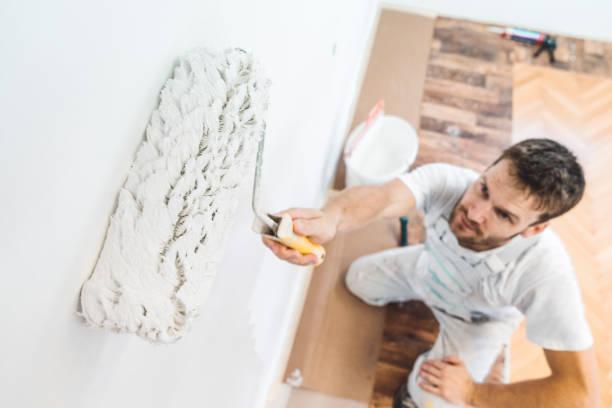 Professioneller Maler hält eine Farbwalze in weißer Wandfarbe einweichen – Foto