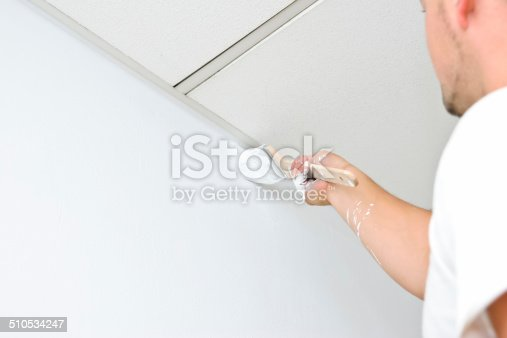 Professional painter painting the edge between wall and ceiling.
