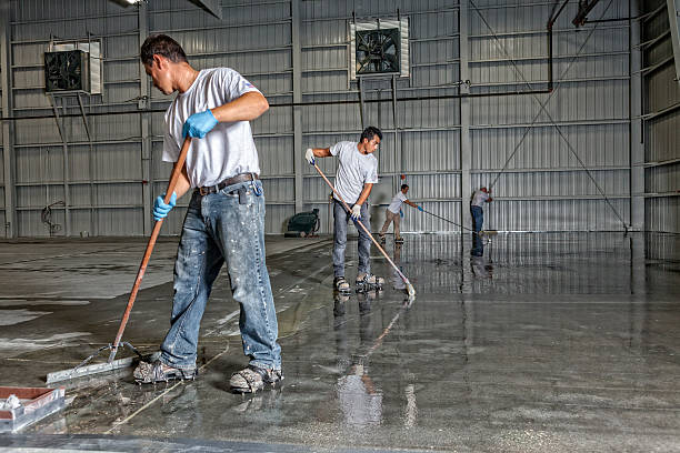 professional painters put down a coating in airport hanger - construction workwear floor bildbanksfoton och bilder