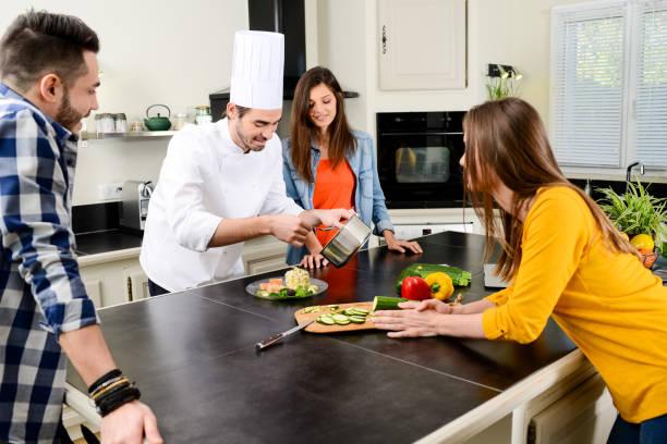 cozinheiro profissional cozinhar em casa de cozinha privativa do cliente dando uma aula de culinária para jovens em casa - soldado raso - fotografias e filmes do acervo