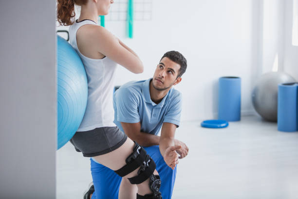 professional personal trainer and sportswoman exercising with ball - sports medicine stock pictures, royalty-free photos & images
