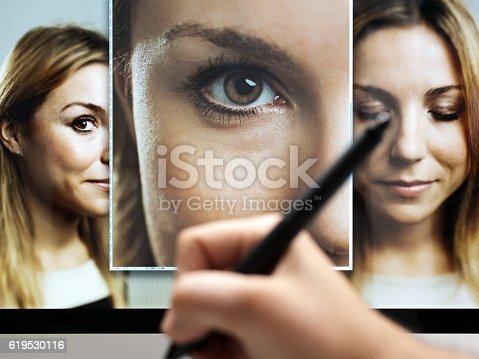 Image of  a hand with professional digital tablet retouching and editing multiple digital photographs of a beautiful woman. Sharp focus on screen. Horizontal image from a DSLR camera.