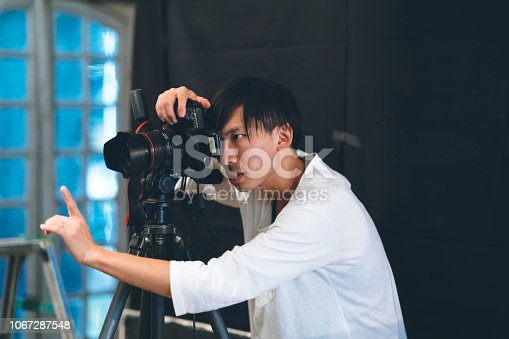 A professional photographer is taking photos in his studio.