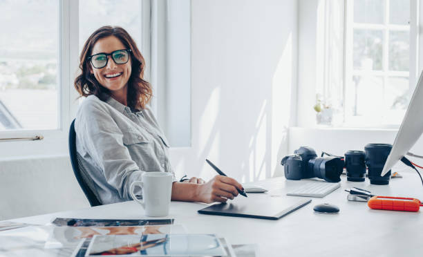 Professional photographer at her office desk Professional photographer sitting at her office desk looking away and smiling. Woman in office with digital graphic tablet and drawing pen. graphic designer stock pictures, royalty-free photos & images