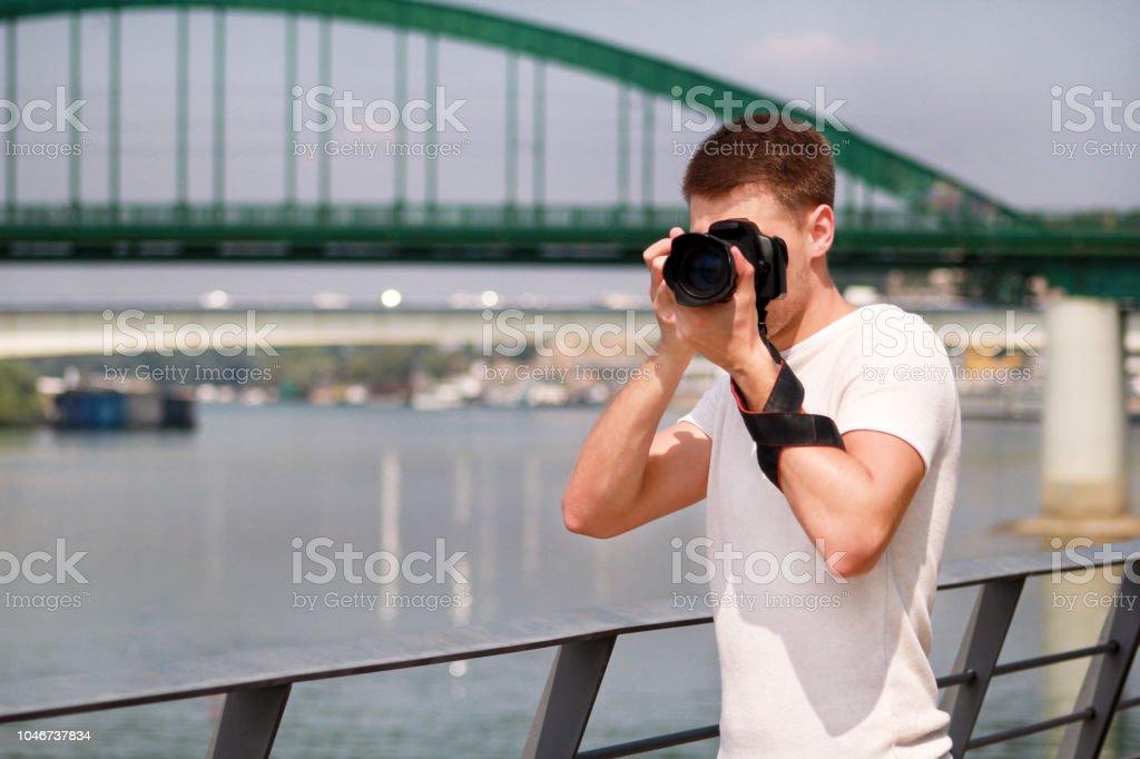 Fotógrafo profissional examinando a paisagem e tirar fotos do meio ambiente, arquitetura, elementos urbanos, Rio, ponte velha de verde. Turista e o viajante é fazer fotografia de paisagem com câmera. - foto de acervo