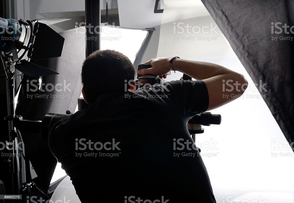 Professional Photographer From Behind Looking Through Viewfinder In Studio stock photo