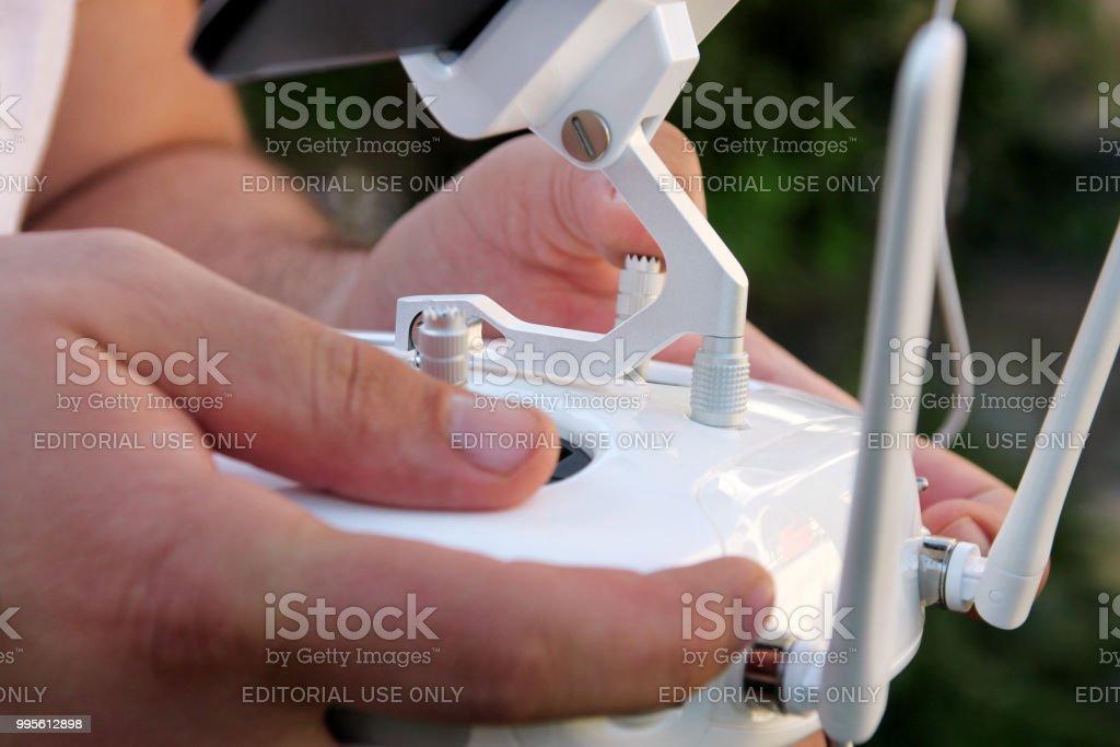 Fotógrafo profissional possui painel de controle remoto com tela e controles prontos para voar quad helicóptero no ar. Homem é usuário das novas tecnologias. - foto de acervo