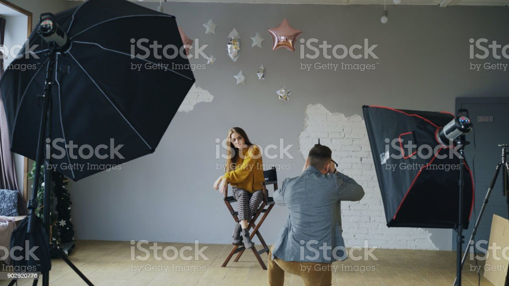 Professional photographer man taking photo of beautiful model girl with digital camera in studio stock photo