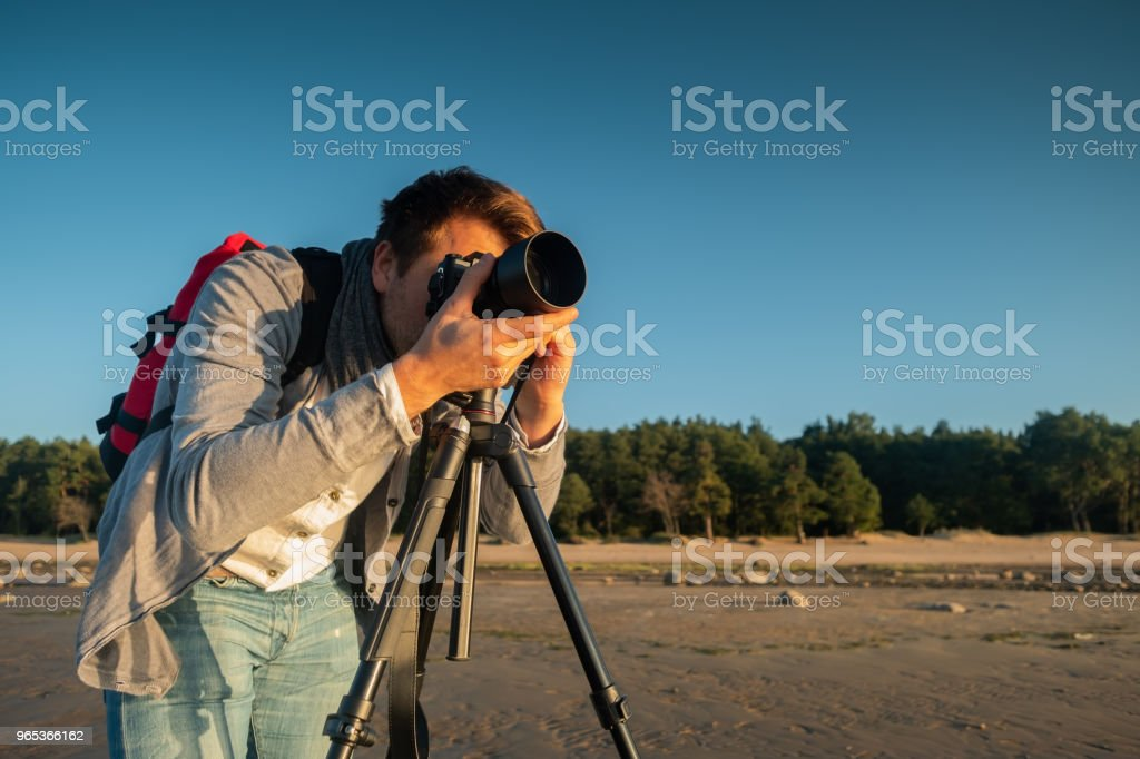 Professional photographer on location and making photo standing with tripod on beach royalty-free stock photo