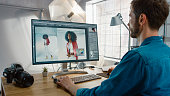istock Professional Photographer Sitting at His Desk Uses Desktop Computer in a Photo Studio Retouches. After Photoshoot He Retouches Photographs of Beautiful Black Female Model in an Image Editing Software 1196171818