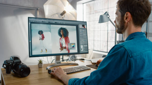 professioneller fotograf, der an seinem schreibtisch sitzt, verwendet desktop-computer in einem fotostudio retusch. nach dem fotoshooting retuschiert er fotos von schönem schwarzen weiblichen modell in einer bildbearbeitungssoftware - fotografische themen stock-fotos und bilder