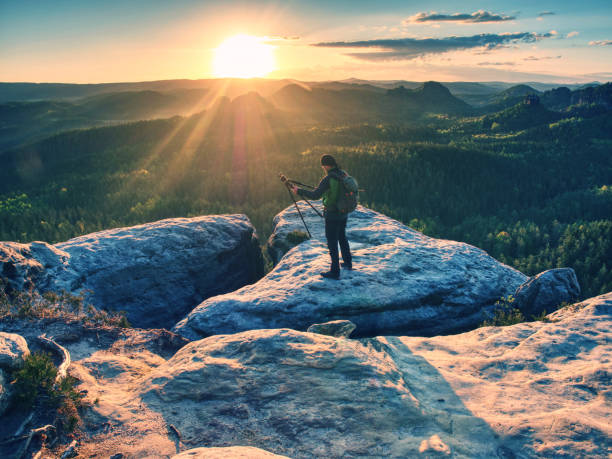Professional photographer stay with tripod on cliff and thinking. stock photo