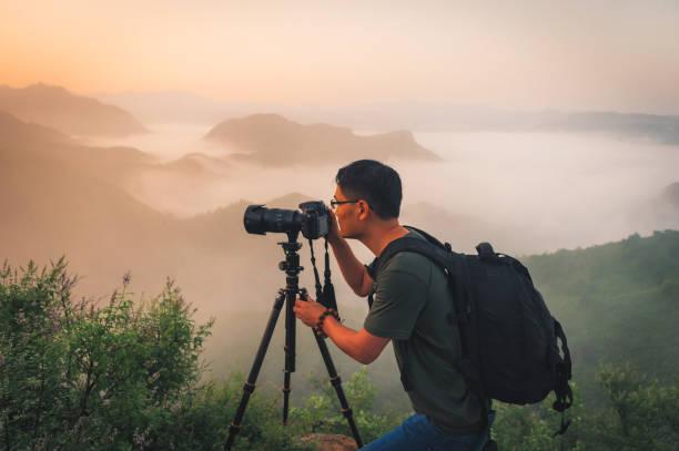 Professional photographer takes photos with camera on tripod stock photo