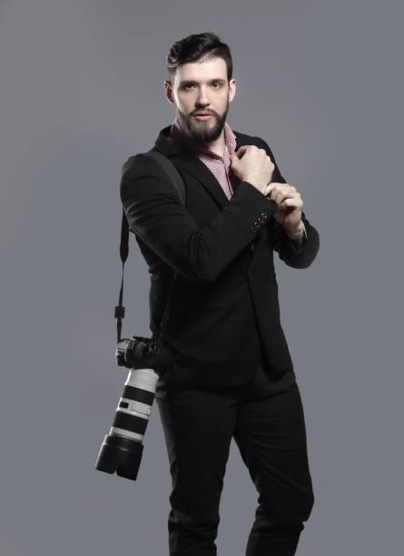 professioneller Fotograf mit Kamera, Einstellen eines Manschettenknöpfes.isolated auf grauem Hintergrund – Foto
