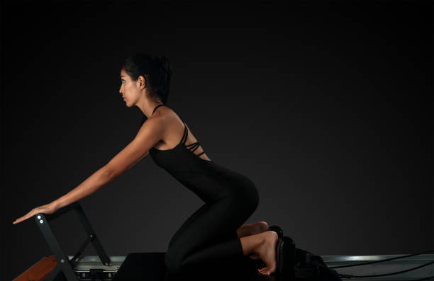 Professional pilates reformer instructor performing pilates moves stock photo