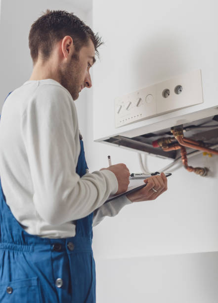 Professional plumber doing a boiler check stock photo