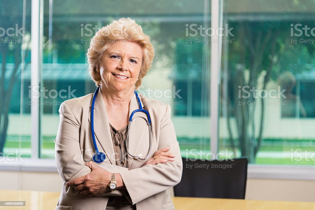 Professional portrait of senior female doctor in office stock photo