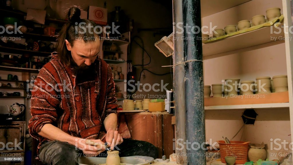 Professional potter carving mug with special tool in pottery workshop stock photo