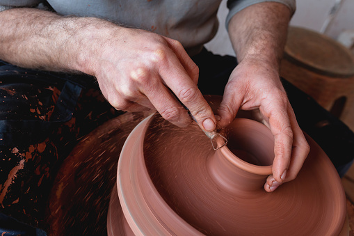 Professional potter making bowl in pottery workshop
