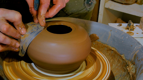 Professional potter shaping bowl with special tool in pottery workshop
