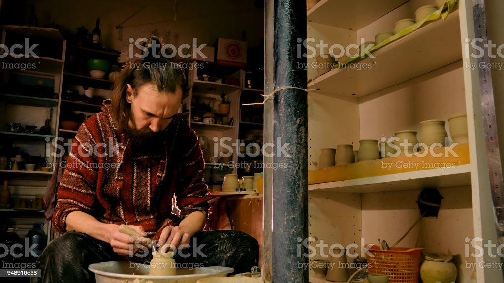 Professional potter shaping mug with special tool in pottery workshop stock photo