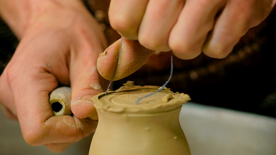 Professional potter shaping mug with special tool in pottery workshop
