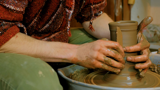 Professional potter shaping part of kettle with special tool in pottery workshop