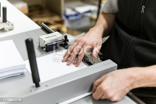 Professional printer manually slicing paper with guillotine.