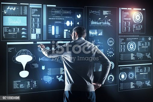 istock Professional programmer standing alone and looking at the screen 921593498
