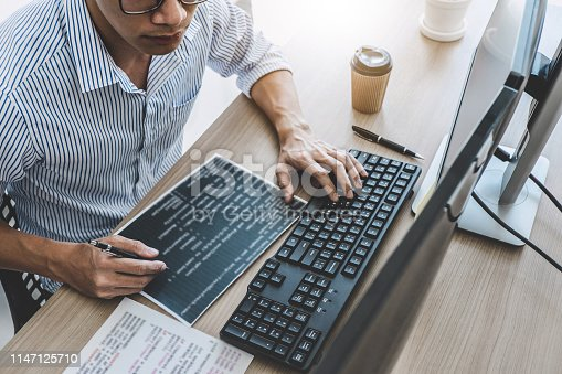 Professional programmer working at developing programming and website working in a software develop company office, writing codes and typing data code.