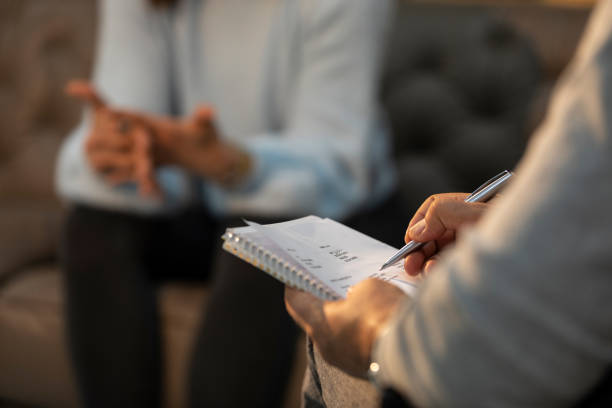 Professional psychologist doctor listening and giving the consult to female patients - Mental health concept stock photo