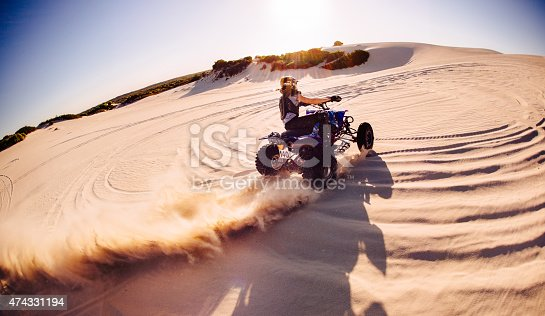 Wide angle view of a professional quad biker racing around a sand dune and kicking up a lot of sand