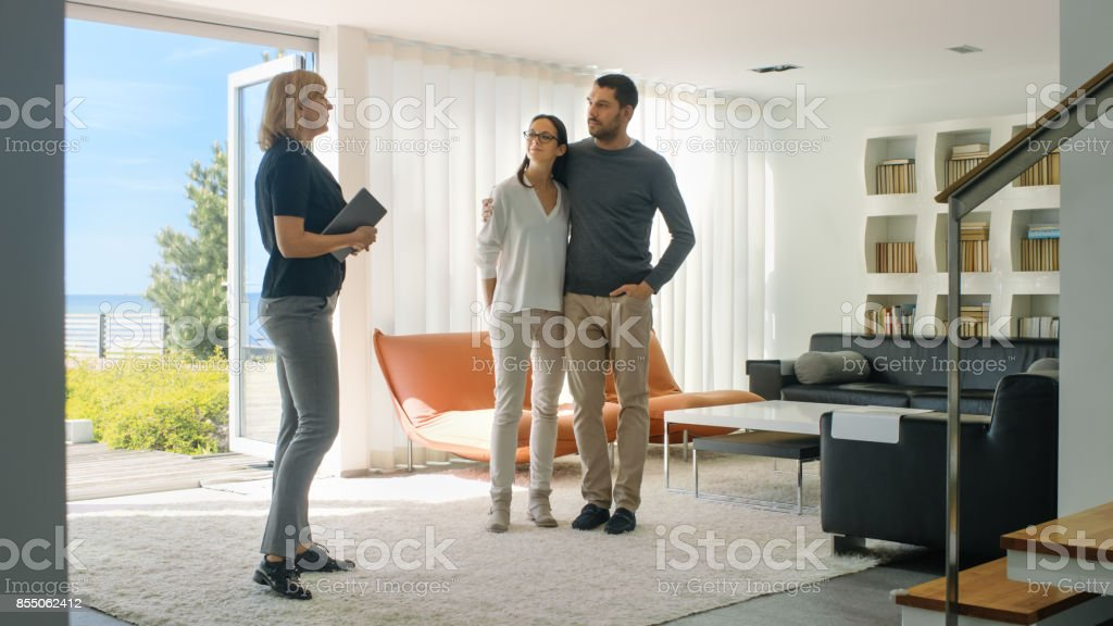 Professional Real Estate Agent Shows Stylish Modern House to a Beautiful Young Couple Who are in the Market for Purchasing/ Renting New Home. House Has Floor to Ceiling Windows and Seaside View. stock photo